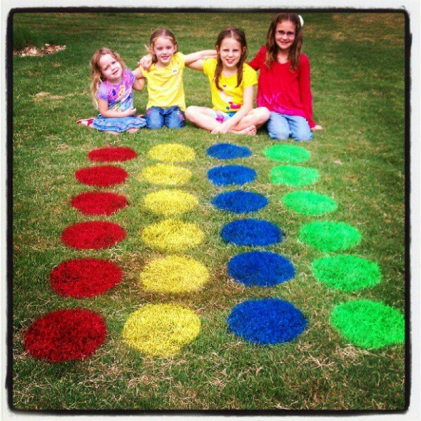Girls sitting behind twister board painted on the grass